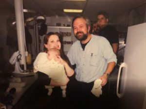 The very first Community Thanksgiving Luncheon in 1999. Jessie McGarty with 7-week old son Jordan and our beloved chef of many years Don Finch.